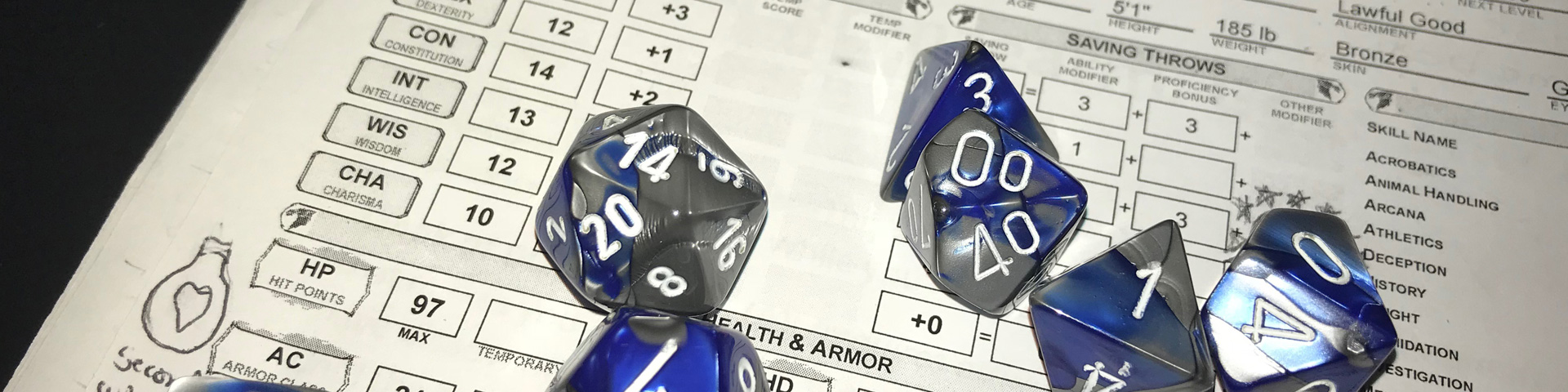 Blue and grey dice set on a D&D character sheet.