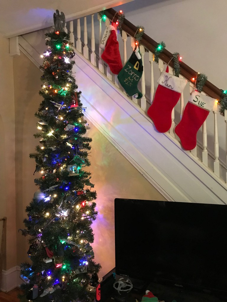 A tall Christmas tree rises next to a set of stairs decked out with stockings. A TV appears to the right.