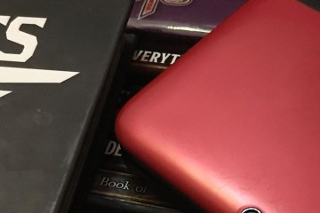 A role-playing game book lays next to a red Nintendo 3DS portable game console. Other RPG source books can be seen beneath the objects.