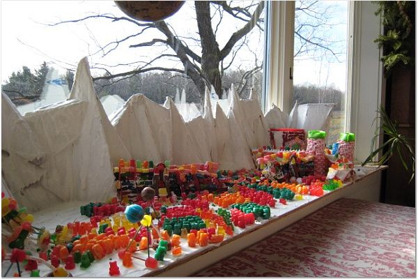 The forces of good and evil (represented as small candies) battle upon a table top. White mountains appear in the background.
