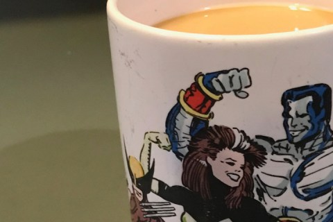 A coffee cup featuring the X-men appears on a green counter top.