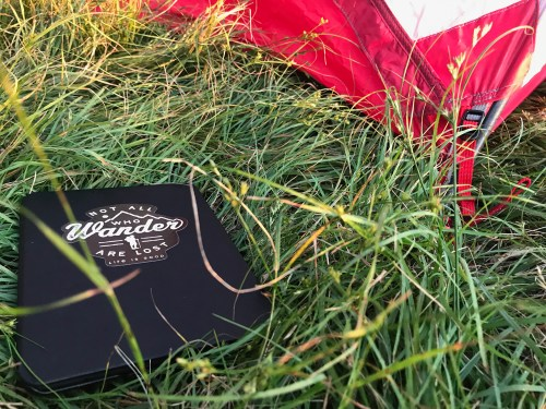 A Kindle in the grass next to a tent.