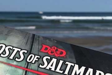 The cover of the Ghosts of the Saltmarsh RPG book appears in front of the ocean.