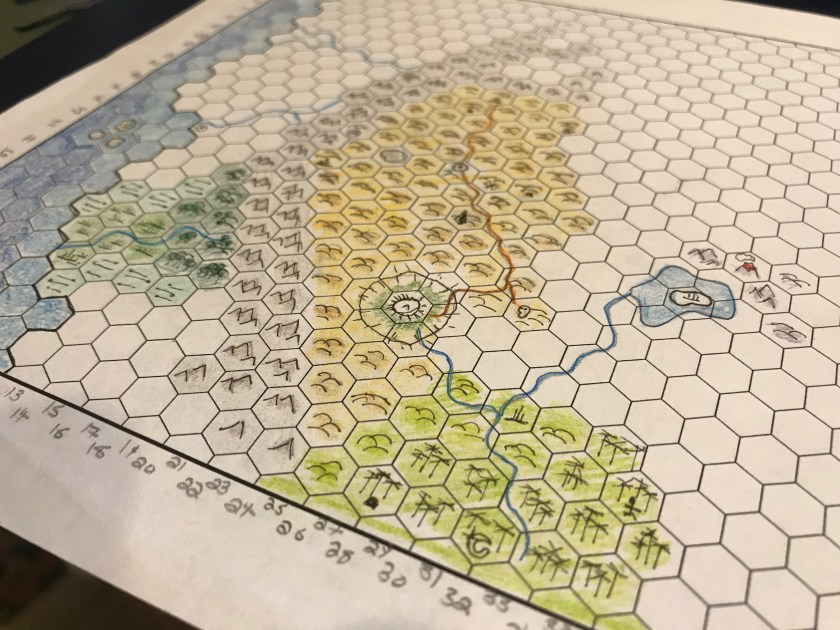 Hex paper with the beginnings of a map on it. Mountains are brown. Hills are yellow shading to green near the bottom of the map. An ocean is visible on the left side of the map.
