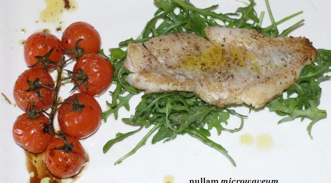 In de pan gebakken vis met oven geroosterde tomaatjes en rucola salade