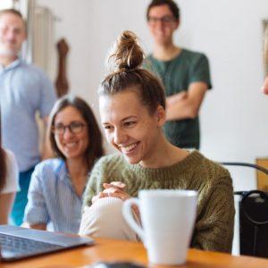 usmiata skupina ľudí nad pracovným stolom s notebookom