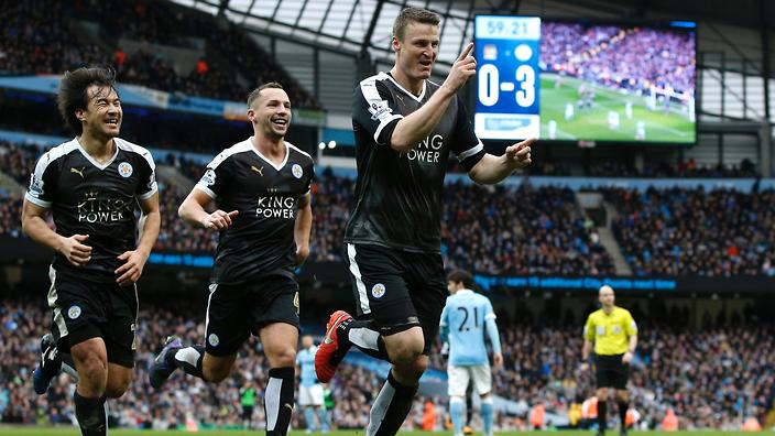 Leicester City's German defender Robert Huth (R) celebrates scoring his team's third goal with Leicester City's Japanese striker Shinji Okazaki (L) and Leicester City's Algerian midfielder Riyad Mahrez during the English Premier League football match between Manchester City and Leicester City at the Etihad Stadium in Manchester, north west England, on February 6, 2016. / AFP / ADRIAN DENNIS / RESTRICTED TO EDITORIAL USE. No use with unauthorized audio, video, data, fixture lists, club/league logos or 'live' services. Online in-match use limited to 75 images, no video emulation. No use in betting, games or single club/league/player publications. / (Photo credit should read ADRIAN DENNIS/AFP/Getty Images)