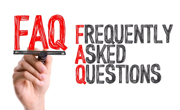 Hand with marker writing the word Frequently Asked Questions