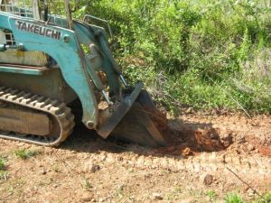 Takeuchi with attachment digging a contour ditch