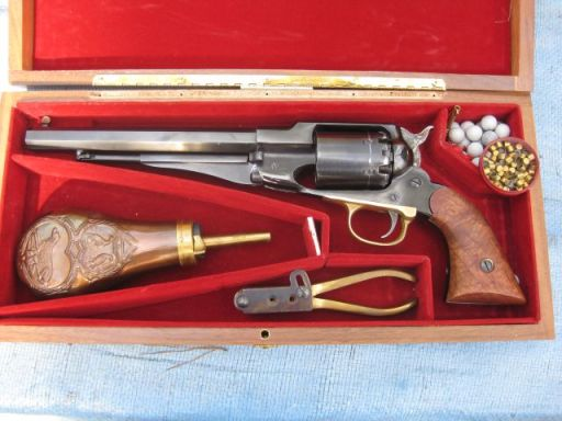 the case contains the revolver, a powder flask, a mould for making your own bullets, the bullets (top right) and the caps (in the tin next the bullets)