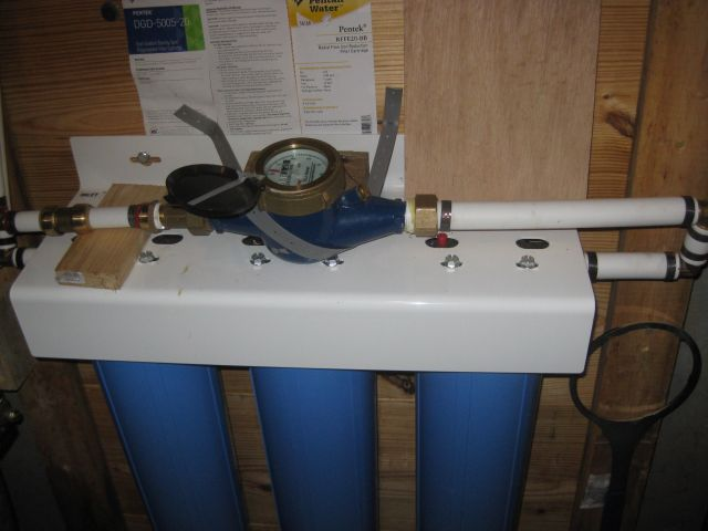 "the new water meter is secured on top of the filter assembly.  1"" pex from filter then 3/4"" pex to house"