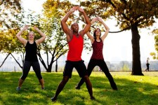 A group of people doing jumping jacks in the park