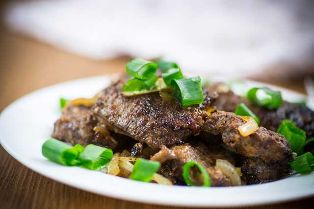 Fried Liver, Onions, and Green Onions On a Plate.