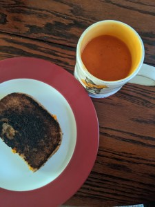 grilled cheese and tomato soup in a mug
