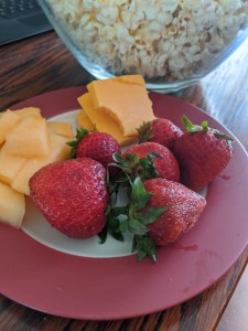 plate with strawberries and cheese and a bowl of popcorn