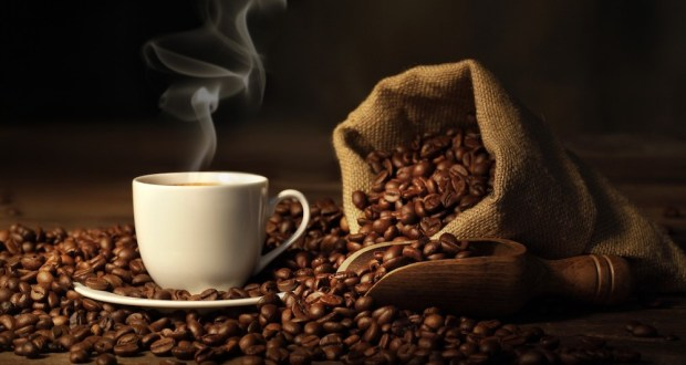 Steaming cup of coffee sits on mound of coffee beans.