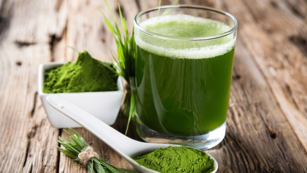 Spirulina powder and drink on rough wood tabletop.