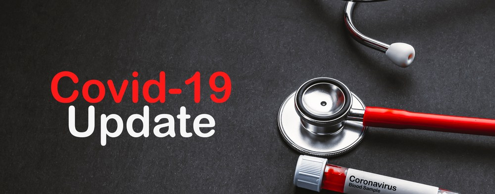 COVID-19 UPDATE text with stethoscope and blood sample vacuum tube on black background