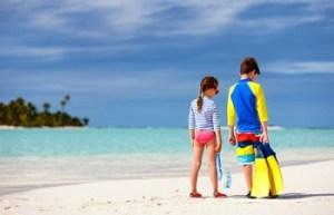 兄妹がラッシュガードを着て、ビーチで遊ぶ