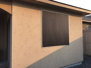 Custom fit black solar screen on Stucco Home