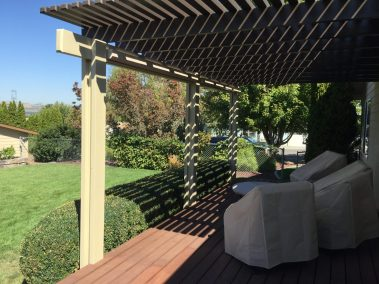 Stucco cable guided sun shades rolled up on Pergola