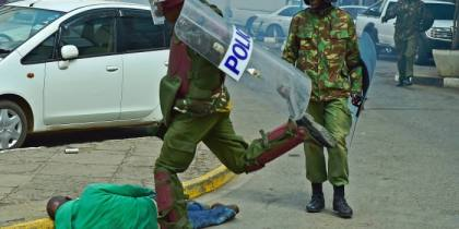 A Kenyan riot police officer kicking a fallen civilian(Photo credit: AFP)