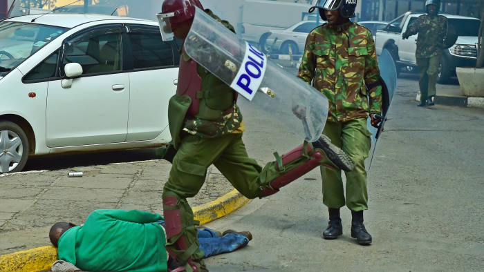 A Kenyan riot police officer kicking a fallen civilian(Photo credit: AFP)