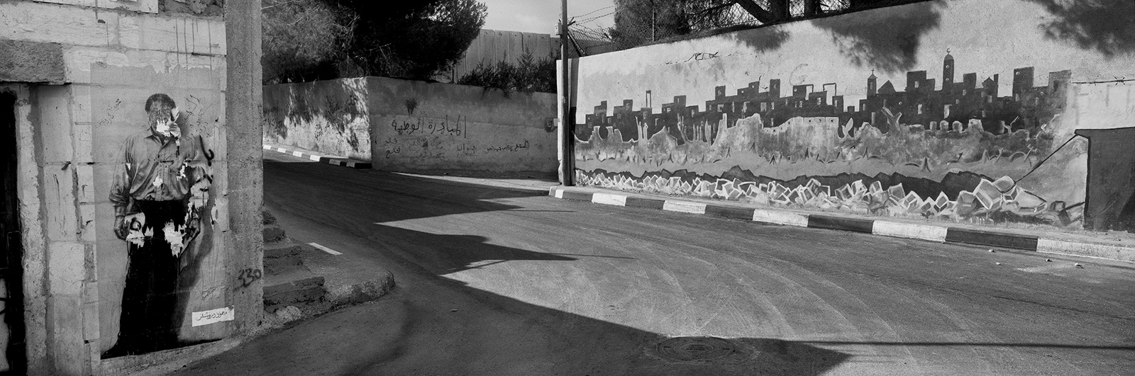 A poster of the Palestinian poet Mahmoud Darwish (left), Aida refugee camp, near Bethlehem, West Bank, 2009; photograph by Josef Koudelka from 'This Place,' an exhibition of pictures by twelve photographers of Israel and the West Bank, at the Brooklyn Museum of Art until June 5, 2016