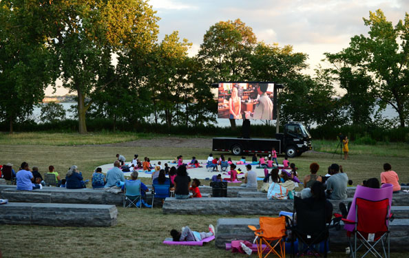 families and friends gather on a lawn and in lawn chairs to watch a movie on a mobile screen