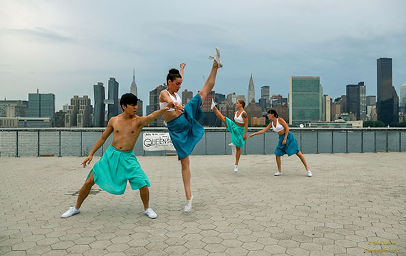 Four dancers perform a routine at the waterfront space which features a view of the Midtown Manhattan skyline.