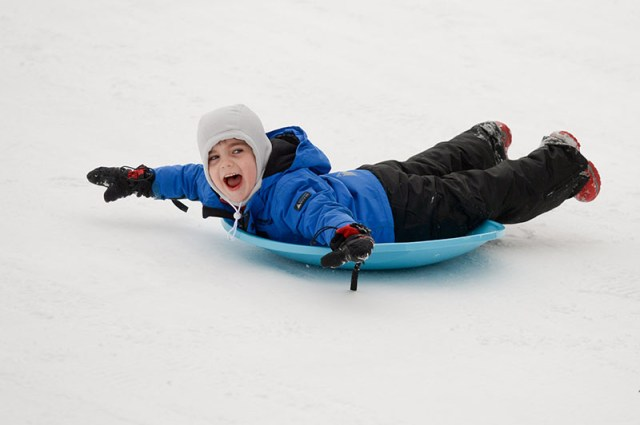 A child happily sleds down a hill covered in snow.