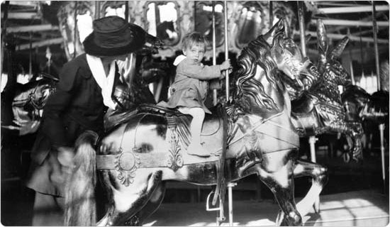 A child holds tight during a ride on Forest Park's Muller Carousel, circa 1940. Courtesy of the Parks Photo Archive, neg. 53148.