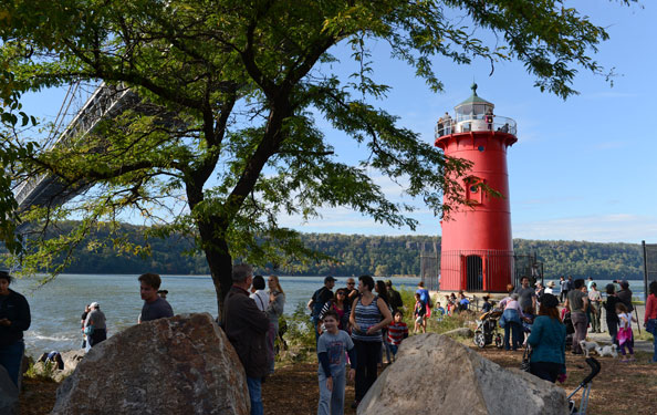 guests visit and hang around a little red lighthouse under a bridge at the water's edge