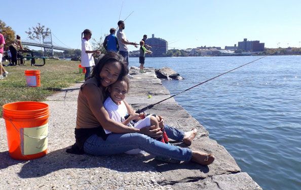 a woman and a child pose for a photo while fishing at the waterfront at Randall's Island