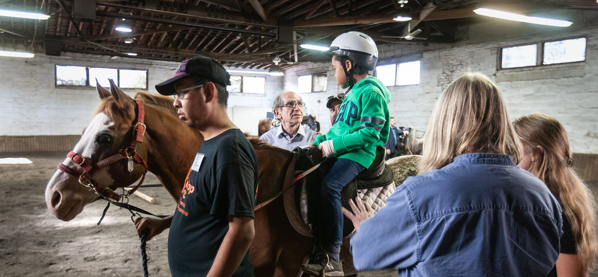 A child experiencing riding on a horse at GallopNYC and talking to a Trust Board member.