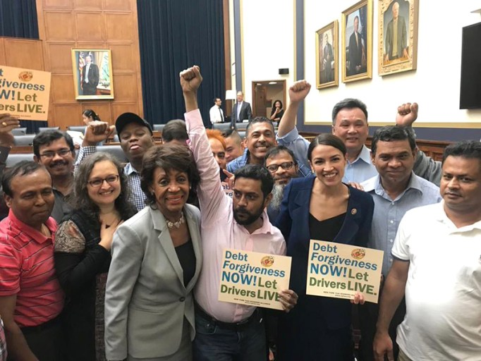 """A group photo with individuals supporting taxi drivers and signs that say, """"Debt Forgiveness NOW! Let Drivers LIVE."""""""