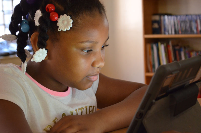 A student at one of the family shelters run by BronxWorks doing her schoolwork online. Photo by Aaron Cipollina/BronxWorks