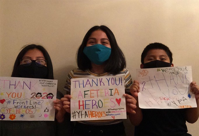 Young students hold up signs thanking Cafeteria Heroes.