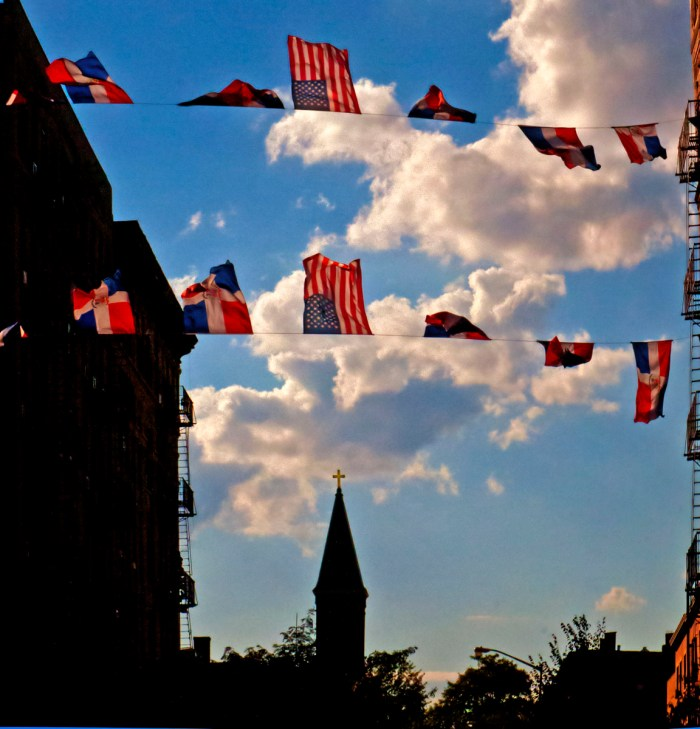 Memorial Day: American and Dominican flags flying over a street in Williamsburg, Brooklyn with a church steeple in the distance.