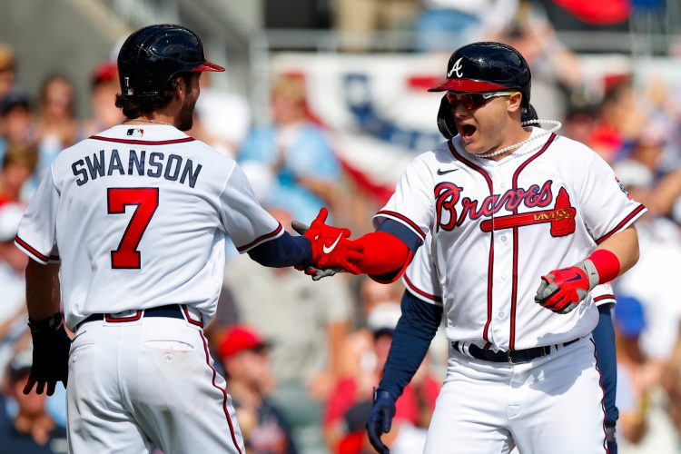 ATLANTA, GEORGIA - OCTOBER 11: Joc Pederson #22 of the Atlanta Braves high fives Dansby Swanson #7 after hitting a three run home during the fifth inning against the Milwaukee Brewers in game 3 of the National League Division Series at Truist Park on October 11, 2021 in Atlanta, Georgia. (Photo by Todd Kirkland/Getty Images)