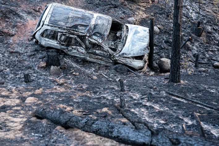 A burned car damaged by the Bootleg Fire is seen here along a mountain road on Wednesday, July 21, 2021, near Bly, Ore.