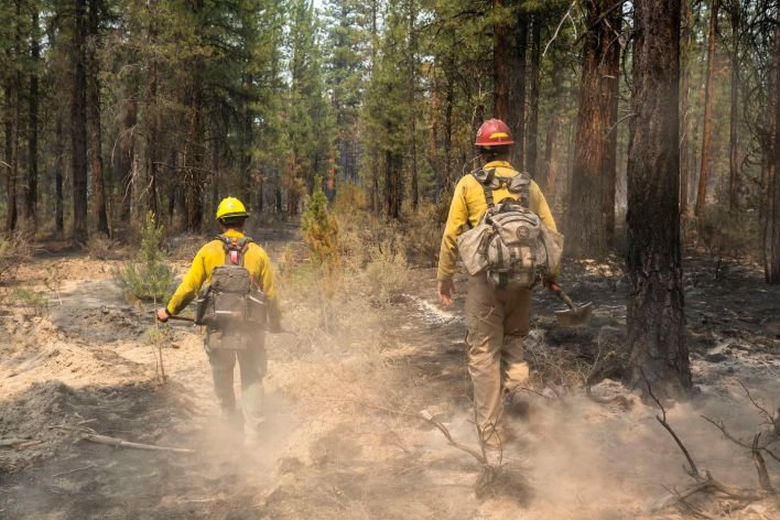 Firefighters Garret Suza, right, and Cameron Taylor, with the Chiloquin Forest Service, search for hot spots on the North East side of the Bootleg Fire on Wednesday, July 14, 2021, near Sprague River, Ore.