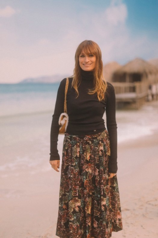 CAROLINE DE MAIGRET, CHANEL Ambassador, wore a floral printed skirt, look 52, with a black wool turtleneck, both from the Fall-Winter 2018/19 Ready-to-Wear collection. CHANEL bag and shoes. CHANEL Fine Jewellery, Coco Crush ring in 18K white and yellow gold and diamonds. CHANEL Makeup