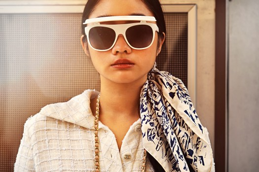 Visor Sunglasses in White, $930 / Hair Accessory in Navy Blue & White Silk Twill, $460 / Tweed Dress in Ecru, $9,590 / Small Vanity with Classic Chain in Pale Pink Grained Shiny Calfskin & Gold-Tone Metal, $2,290 (worn around neck). On lips: Rouge Allure in 117 Or Cuivré, $56.