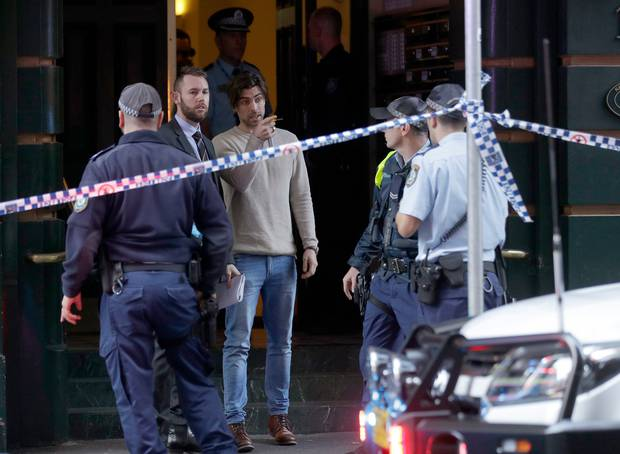 A man, centre , points as he assists police at a building where a woman was found stabbed to death. Photo / AP