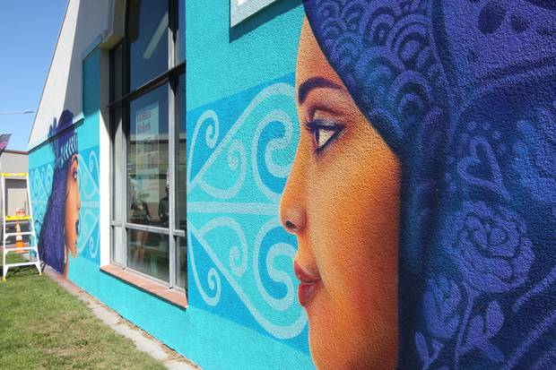 Auckland street artist Erika Pearce has spent the last five days piecing together the culturally diverse mural on the side of Hastings Library. Photo / Paul Taylor