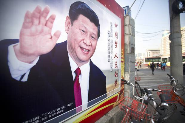 People walk past a propaganda billboard showing Chinese President Xi Jinping along a street in Beijing. The annual meetings of China's top legislative bodies are underway. Photo / AP
