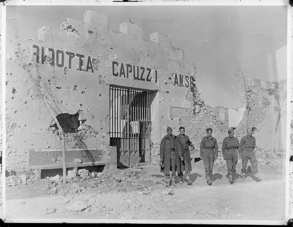 New Zealand soldiers stand in front the battle-scarred Fort Capuzzo in Libya, circa December 1941. The Italian frontier fort had fallen to the New Zealand Division on 22 November during the initial stages of Operation Crusader. Alexander Turnbull Library Reference: DA-02020