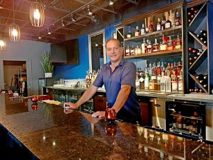 Donny Greco stands behind the bar in Donny G's Lounge and Event Space.