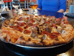 A customized tavern style pizza with cup and char pepperoni and house spiced sausage.